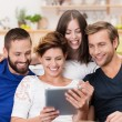 Group of happy friends sharing a tablet — Stock Photo