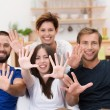 Laughing group of young people with upheld hands — Stock Photo