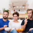 Stock Photo: Group of friends watching gripping movie