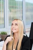 Attractive businesswoman sitting thinking — Stock Photo