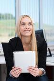 Smiling businesswoman sitting thinking — Stock Photo