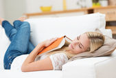 Tired young woman taking a nap at home — Stock Photo