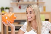 Happy young woman looking at her piggy bank — Stock Photo