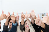 Group of businesspeople giving a thumbs up — Stock Photo