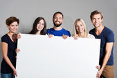 Business team holding a blank sign — Stock Photo