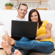Barefoot young couple relaxing with a laptop — Stock Photo