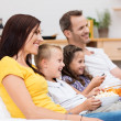 Happy young family watching television — Stockfoto