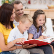 Happy family reading a book together — Stockfoto