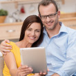 Happy couple smiling and reading their tablet-pc — Stock Photo