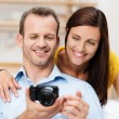 Laughing young couple looking at a photograph — Stock Photo