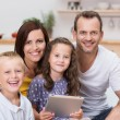 Happy young family relaxing with a tablet-pc — Stock Photo #34576669