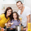Cute young girl cooking with her parents — Stock Photo