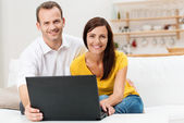 Smiling couple using a laptop computer — Stock Photo
