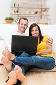 Barefoot young couple relaxing with a laptop — Photo