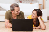 Happy couple sharing a laptop — Stock Photo