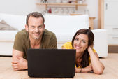 Natural smiling couple relaxing with a laptop — Stock Photo