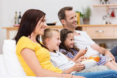 Happy young family watching television — Stock Photo