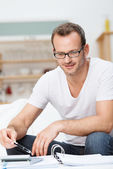 Smiling man totalling up his accounts — Stockfoto