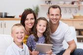 Felice giovane famiglia rilassante con un tablet pc — Foto Stock