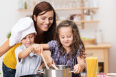 Small brother and sister cooking a meal — Stock Photo