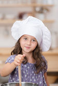 Cute little girl in a white chefs toque — Stock Photo