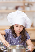 Small girl in a chefs toque cooking in the kitchen — Stock Photo