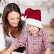 Little boy helping his mother baking Xmas cookies — Stock Photo