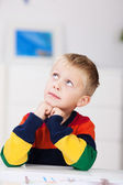 Little boy sitting thinking — Stock Photo