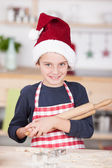 Cute young boy in a Santa Hat in the kitchen — Stock Photo
