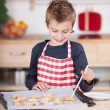 Stock Photo: Happy little boy glazing cookies