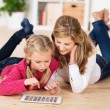 Mother and daughter playing with a tablet — Stok fotoğraf