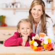 Smiling little girl with her mother and flowers — Stock Photo