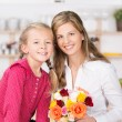 Smiling mother and daughter with a bunch of roses — Stock Photo