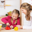 Mother watching her daughter prepare the meal — Stock Photo