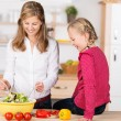 Smiling mother and daughter preparing a salad — Foto Stock