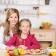 Stock Photo: Pretty little girl helping prepare a fruit salad