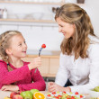 Adorable little girl feeding her mother — Stock Photo
