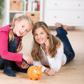Young Mum teaching her daughter to save — Stock Photo