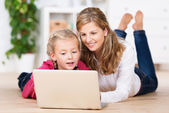 Beautiful young mother teaching her little girl — Stock Photo