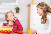 Cute little girl tasting the vegetables — Stock Photo