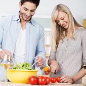 Happy couple preparing a fresh salad — Stock Photo