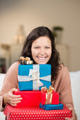 Joyful woman with a pile of Christmas gifts — Stockfoto