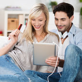 Happy couple purchasing items online — Photo