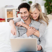 Happy young couple using a laptop computer — Stock Photo