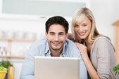 Дружелюбно улыбается пара с ноутбуком — Стоковое фото