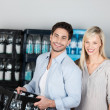 Attractive healthy couple buying bottled water — Stock Photo #35033981