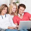 Smiling teenage friends social networking — Stock Photo #35501315