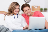 Affectionate teenage couple relaxing with a laptop — Stock Photo
