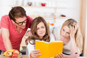 Three young people trying to understand a book — Stock Photo