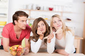 Three young friends undecided on what to cook — Stock Photo